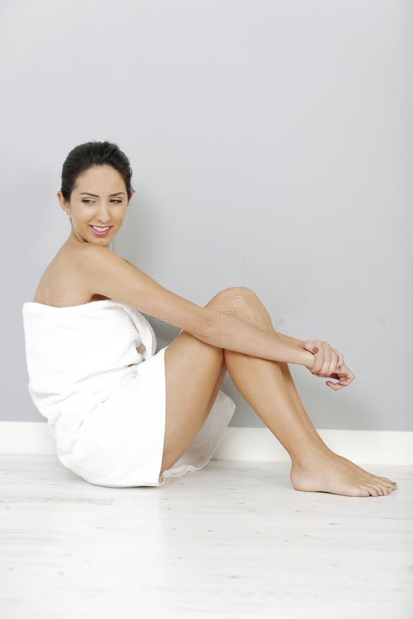 Vrouwenzitting in badhanddoek royalty-vrije stock afbeelding