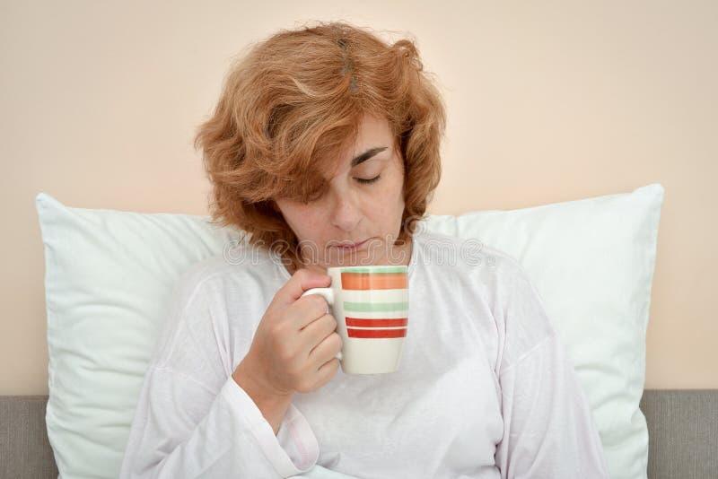 Vrouwenzitting in bed en holding een mok royalty-vrije stock foto's