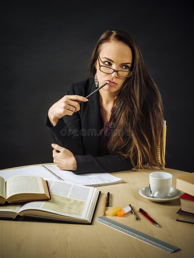 Vrouwenzitting bij haar bureau het denken stock fotografie