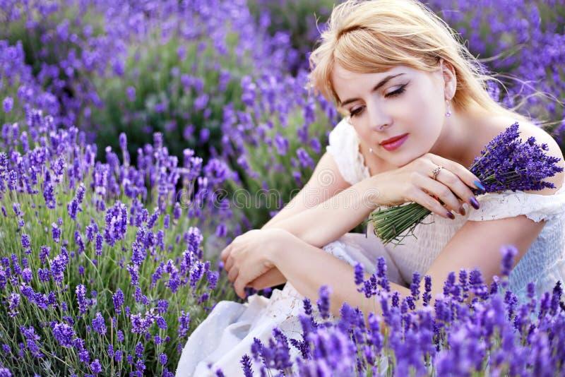 Vrouwenzitting bij lavendelgebied in witte kleding royalty-vrije stock afbeeldingen
