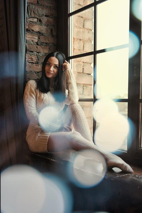 Vrouwenzitting dichtbij venster, licht gloedonduidelijk beeld royalty-vrije stock afbeelding