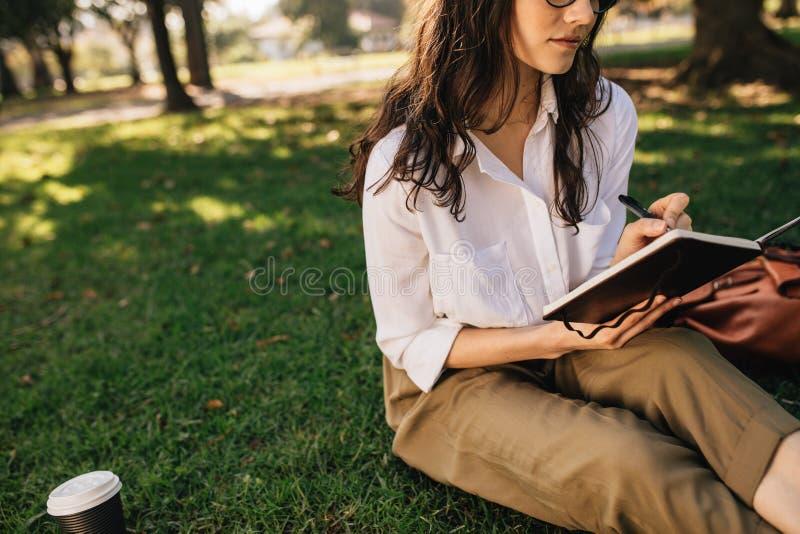 Vrouwenzitting die op gras bij park met boek nota's maken Het vrouwelijke ontspannen in openlucht bij park en het schrijven in ee royalty-vrije stock foto's