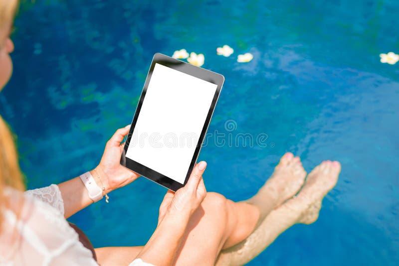 Vrouwenzitting door de pool en het gebruiken van tabletcomputer Verticale het schermrichtlijn royalty-vrije stock fotografie