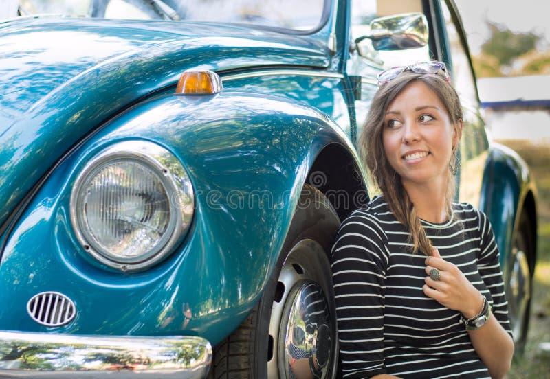 Vrouwenzitting door een oude auto stock foto