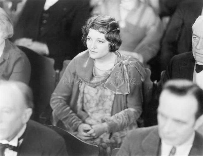 Vrouwenzitting in een auditorium die met gevouwen handen luisteren (Alle afgeschilderde personen leven niet langer en geen landgo stock foto's