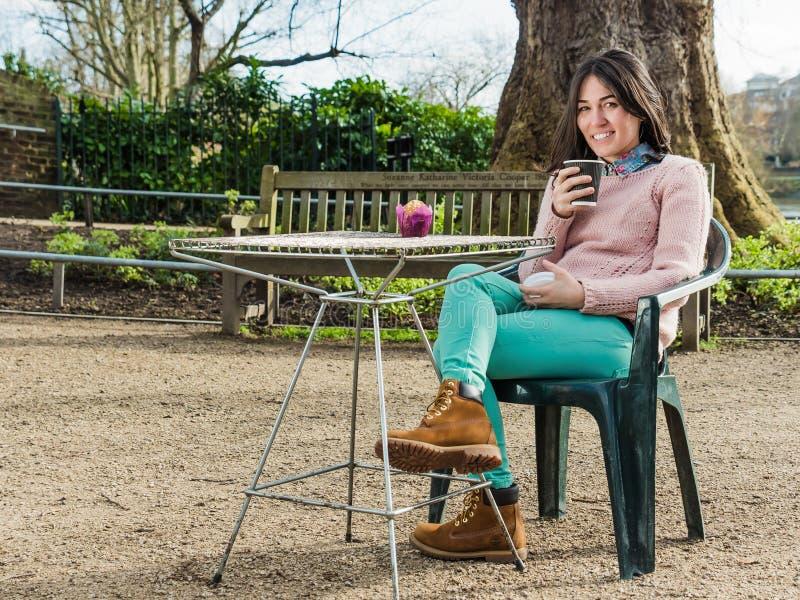 Vrouwenzitting in een Koffie en het Bekijken Camera met een Glimlach royalty-vrije stock fotografie