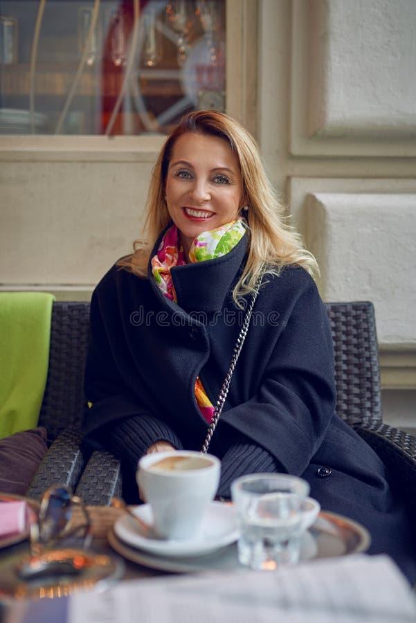 Vrouwenzitting in een restaurant het drinken koffie stock afbeelding