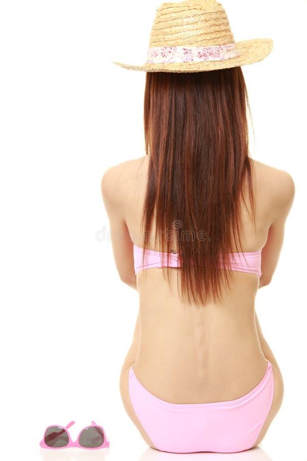 Vrouwenzitting in een roze bikini royalty-vrije stock fotografie