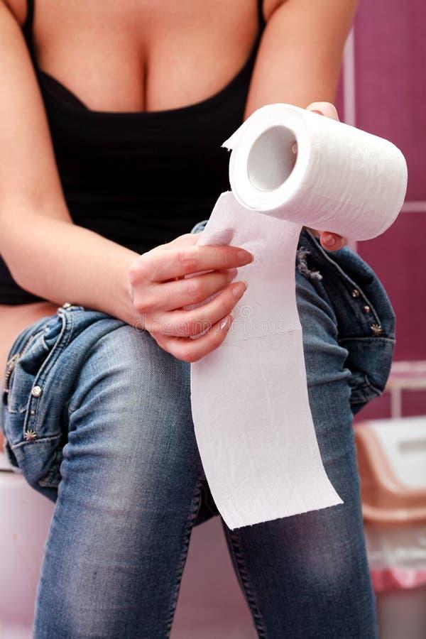 Vrouwenzitting in een toiletruimte stock foto