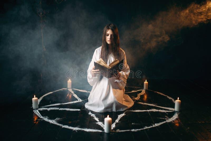 Vrouwenzitting in het centrum van pentagramcirkel royalty-vrije stock fotografie