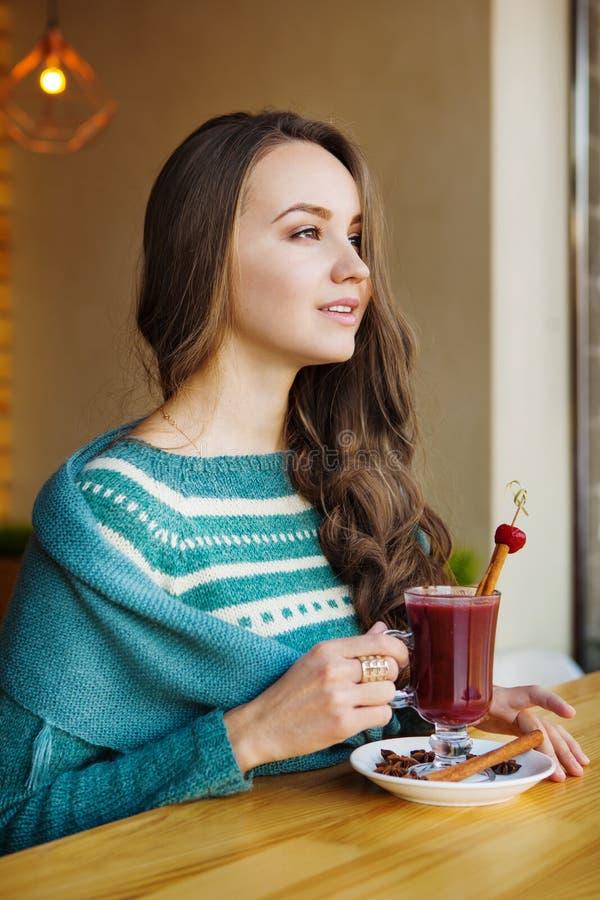 Vrouwenzitting in koffie en het genieten van van haar smoothie stock foto's
