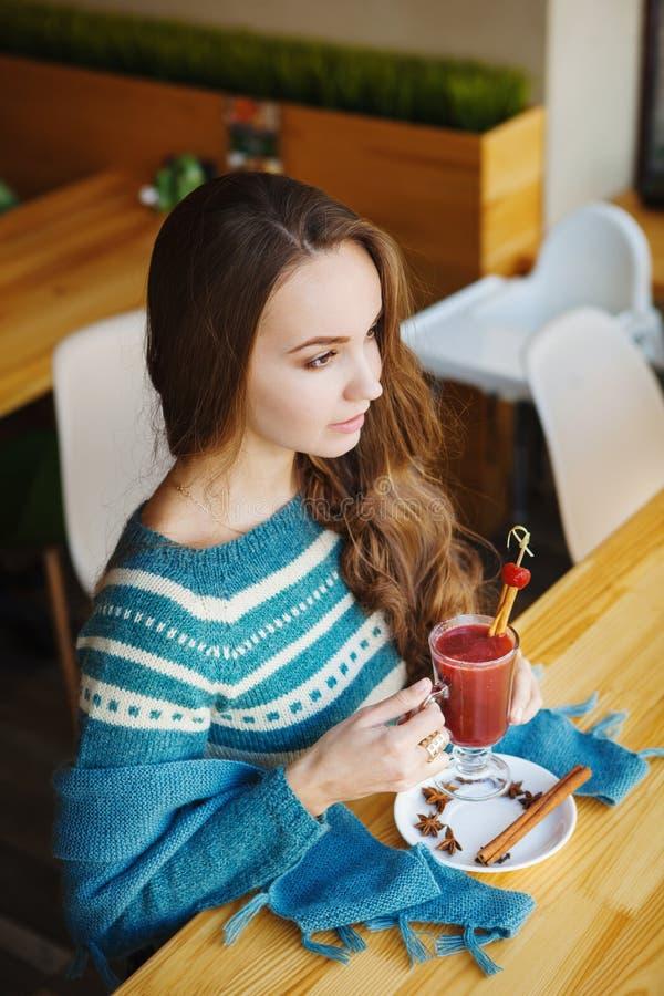 Vrouwenzitting in koffie en het genieten van van haar smoothie royalty-vrije stock afbeelding
