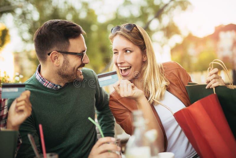 Vrouwenzitting in koffie met de knappe mens en kleurrijke het winkelen zakken stock foto's