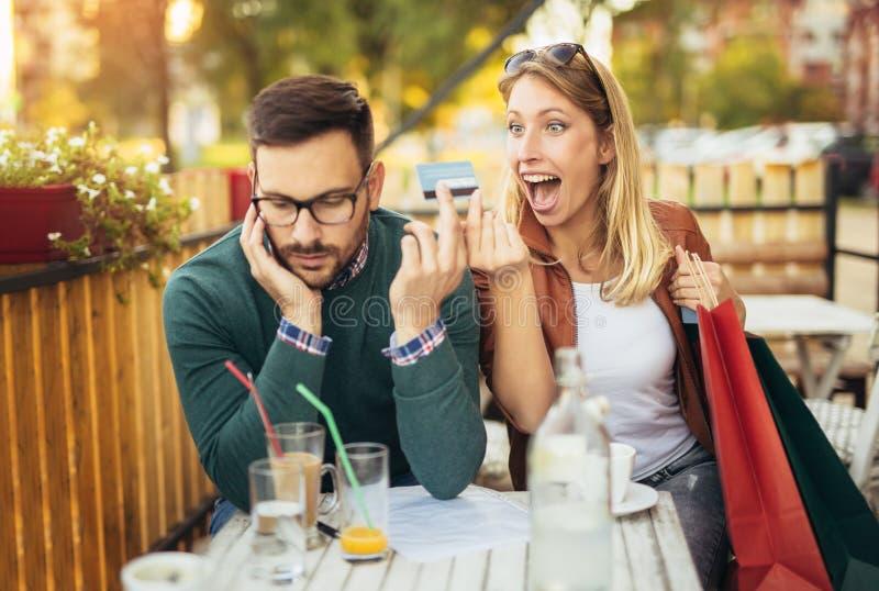 Vrouwenzitting in koffie met de knappe mens en kleurrijke het winkelen zakken stock foto