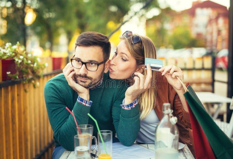 Vrouwenzitting in koffie met de knappe mens en kleurrijke het winkelen zakken royalty-vrije stock afbeeldingen