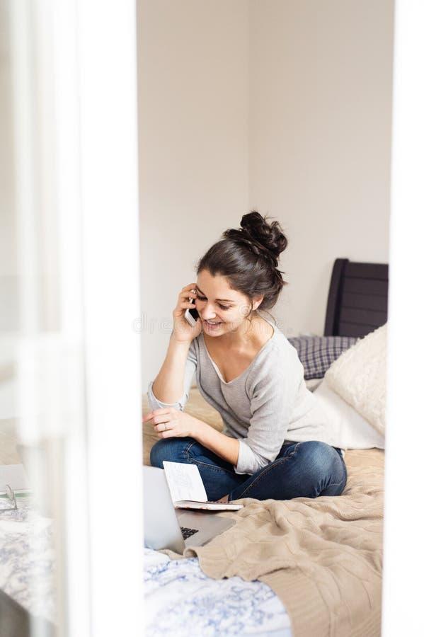 Vrouwenzitting op bed, die telefoongesprek maken Computer op witte achtergrond royalty-vrije stock afbeelding
