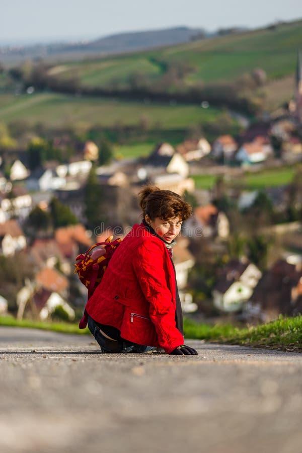 Vrouwenzitting op de lente van het wegportret stock afbeelding