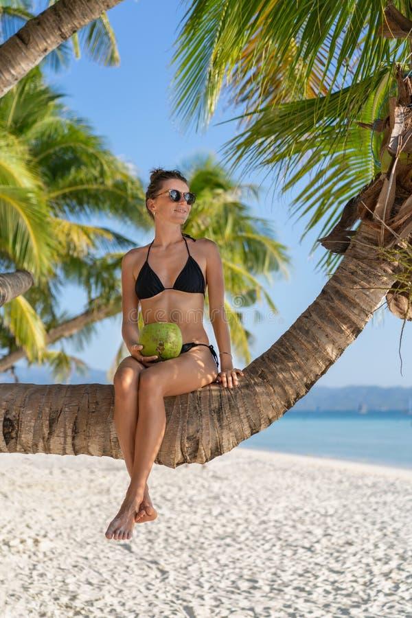 Vrouwenzitting op de palm die en van wit zandstrand ontspannen genieten royalty-vrije stock afbeelding