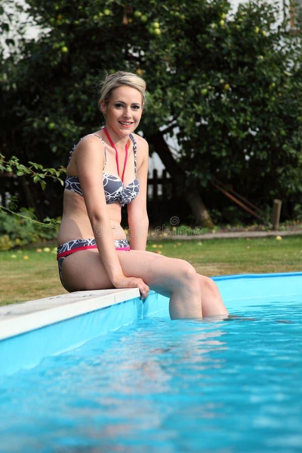 Vrouwenzitting op de rand van een zwembad stock afbeeldingen