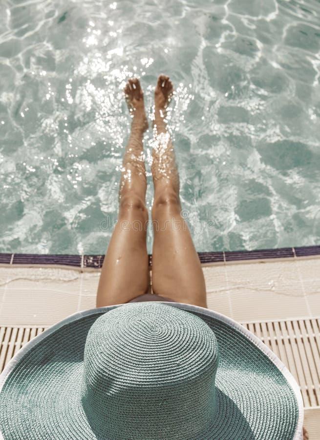 Vrouwenzitting op de rand van zwembad royalty-vrije stock foto