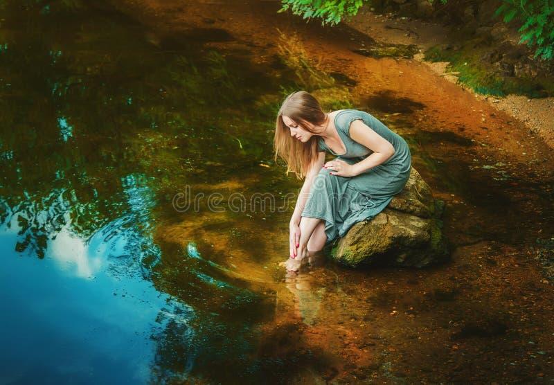 Vrouwenzitting op de rots in een vijver stock foto's
