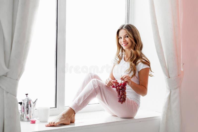Vrouwenzitting op de vensterbank en het eten van druiven royalty-vrije stock foto's