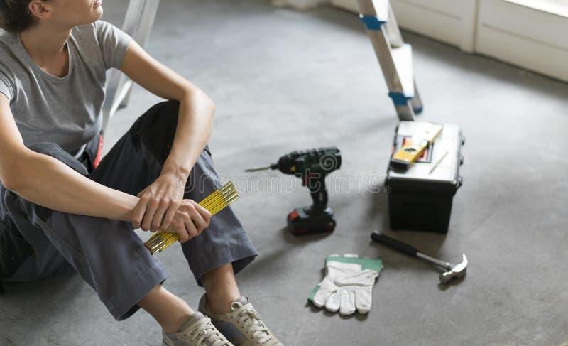 Vrouwenzitting op de vloer en de planning van een huisvernieuwing stock fotografie
