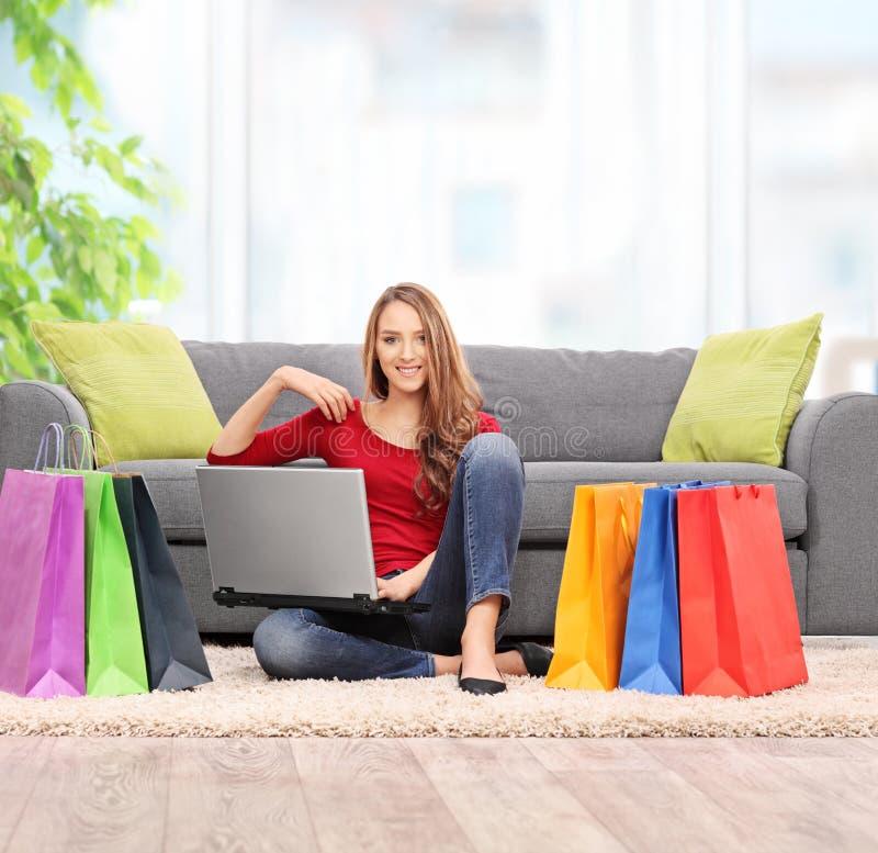 Vrouwenzitting op de vloer met een bos van het winkelen zakken royalty-vrije stock fotografie