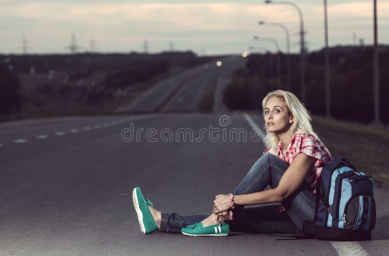 Vrouwenzitting op de weg royalty-vrije stock fotografie