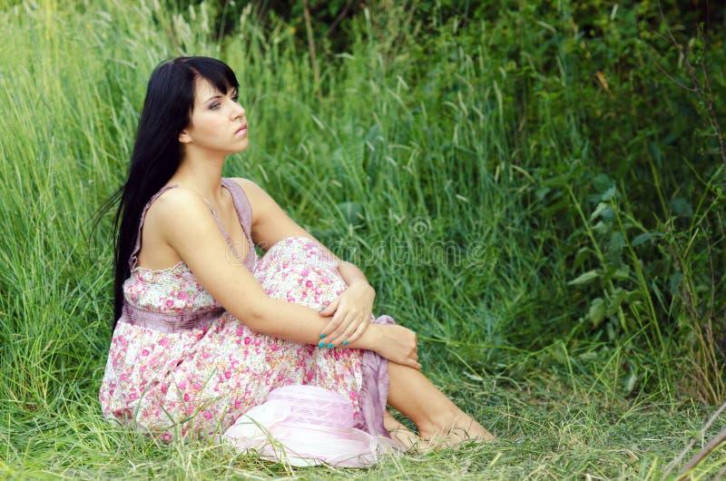 Vrouwenzitting op de de zomerweide stock afbeeldingen