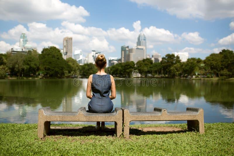 Vrouwenzitting op een bank en het bekijken meer in stadspark stock afbeelding