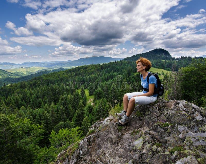 Vrouwenzitting op een bergpiek royalty-vrije stock foto