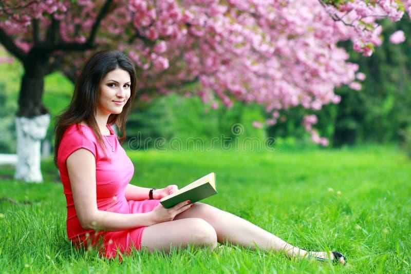 Vrouwenzitting op een gras stock fotografie