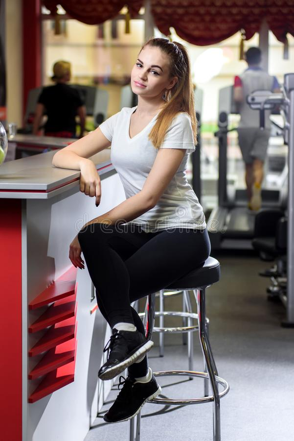 Vrouwenzitting op een hoge stoel in een geschiktheidsstudio stock afbeeldingen