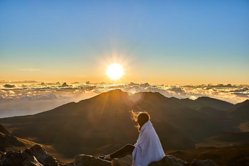 Vrouwenzitting op een rots die van de zonsopgangmening genieten bij de bovenkant van de berg van HaleakalÄ  stock foto's