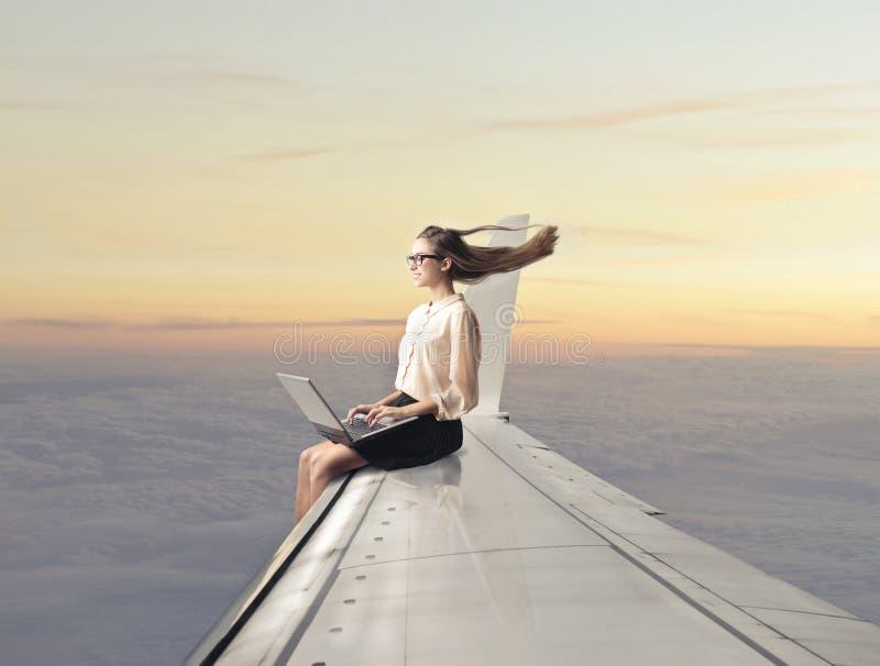 Vrouwenzitting op een vliegtuigvleugel stock fotografie