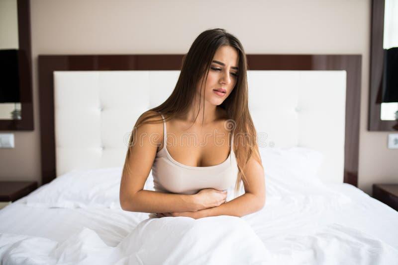 Vrouwenzitting op het bed met pijn royalty-vrije stock foto