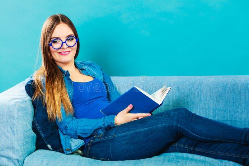 Vrouwenzitting op het boek van de laaglezing thuis royalty-vrije stock afbeeldingen