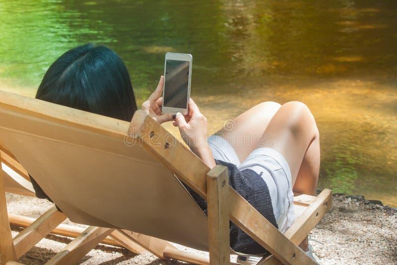 Vrouwenzitting op houten bank naast de rivier en de holding van haar smartphone stock foto