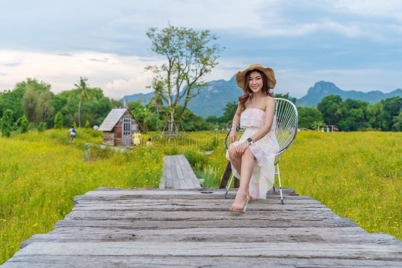Vrouwenzitting op houten brug met het gele gebied van de kosmosbloem royalty-vrije stock foto