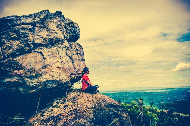 Vrouwenzitting op keien, hemel met bewolkt, openlucht Dwarsproce stock foto's
