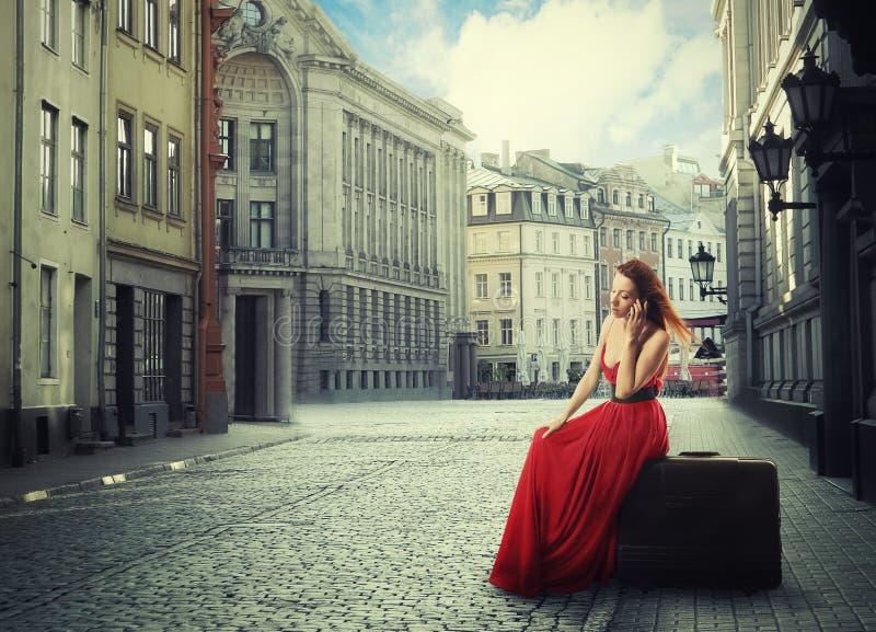 Vrouwenzitting op koffer die op telefoon op stille oude stadsstraat spreken stock afbeeldingen
