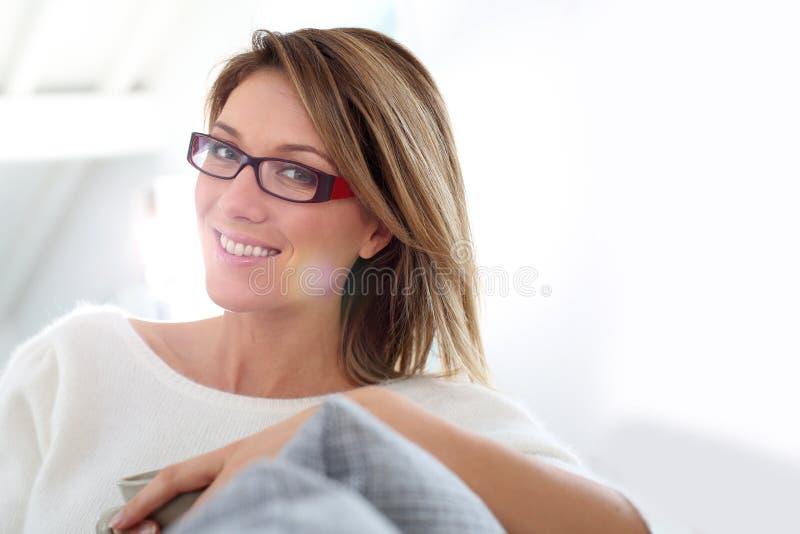 Vrouwenzitting op middelbare leeftijd op bank stock fotografie