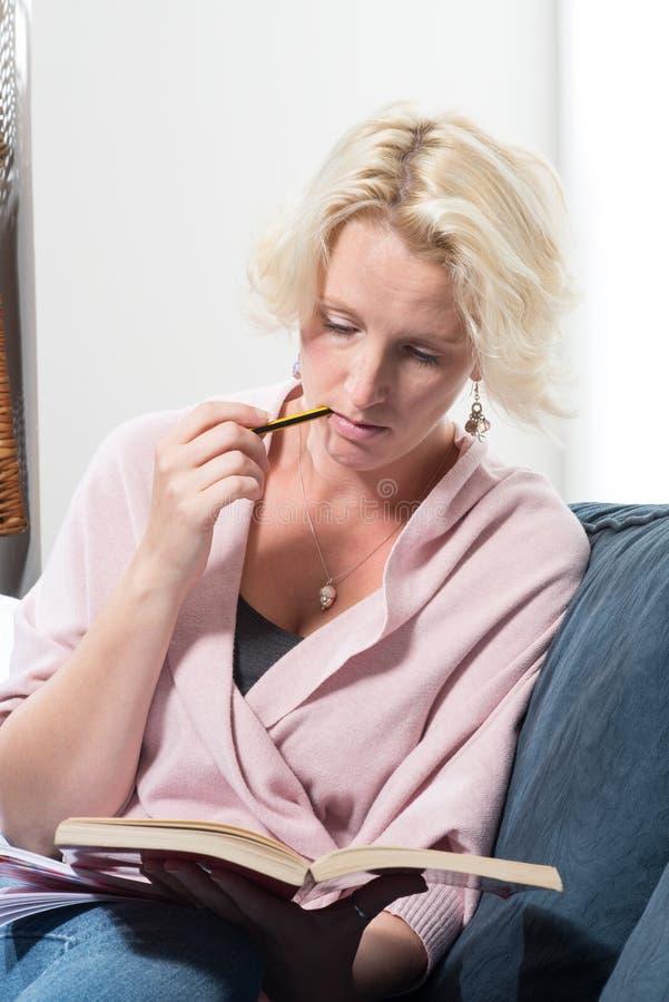 Vrouwenzitting op Sofa Bites Pencil Whilst Reading-Boek stock afbeelding