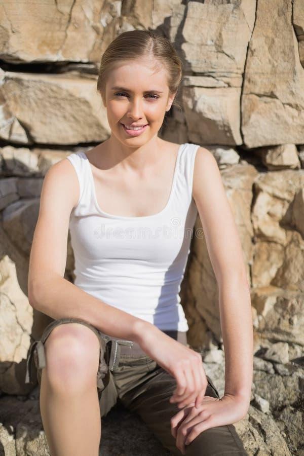 Vrouwenzitting op steen met handen op been royalty-vrije stock foto's