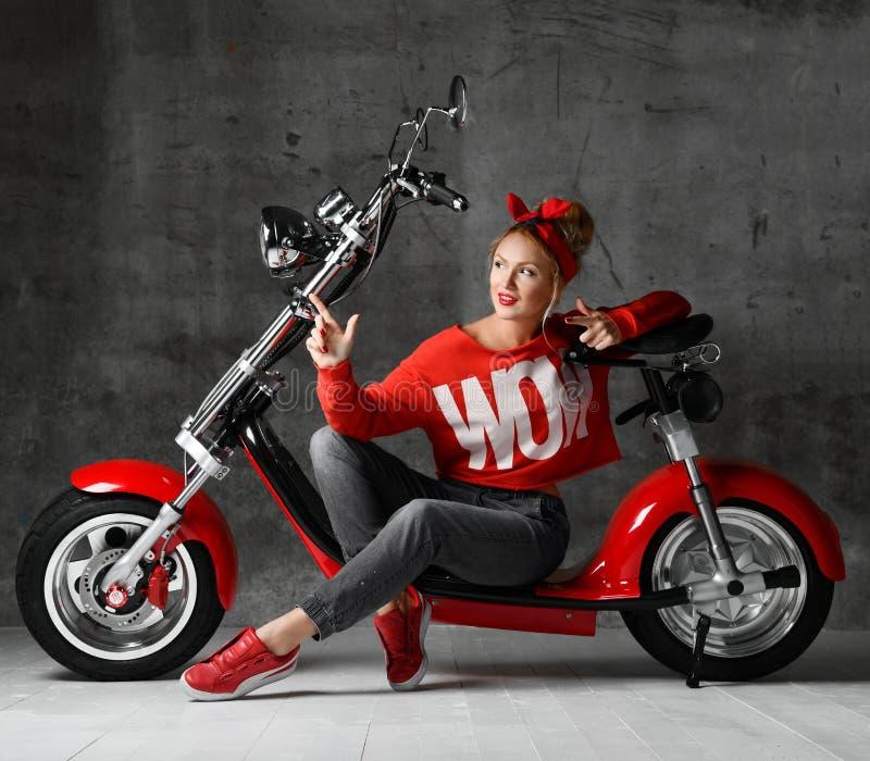 Vrouwenzitting op stijl die van de autoped retro pinup van de motorfietsfiets vinger richten op de hoek in rode blouse en jeans stock foto