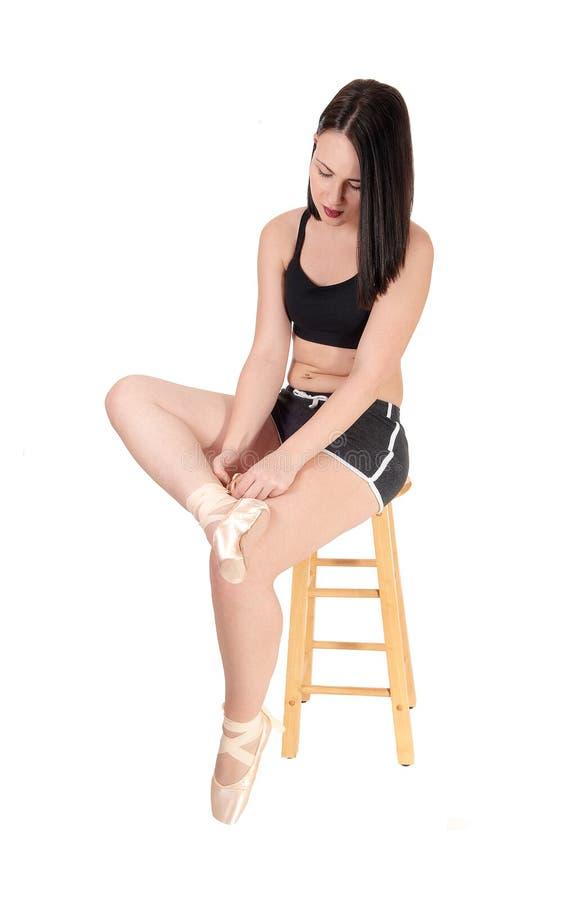 Vrouwenzitting op stoel die haar balletschoen verbinden stock foto