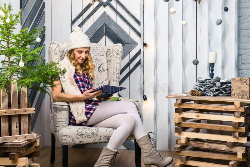 Vrouwenzitting op stoel en lezing een boek in de verfraaide ruimte stock afbeeldingen