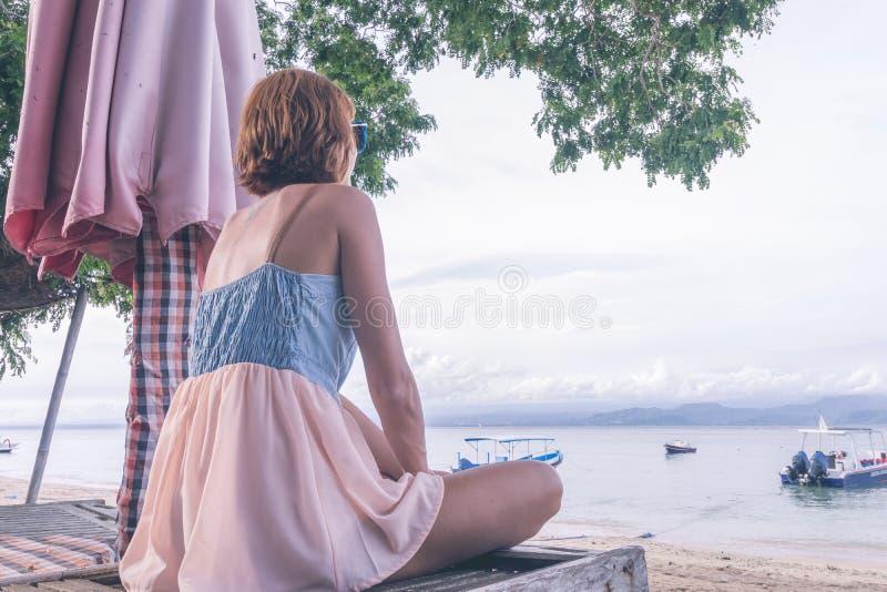 Vrouwenzitting op strand in ligstoel op een bewolkte dag Het eiland van Nusalembongan, Bali, Indonesië royalty-vrije stock foto's