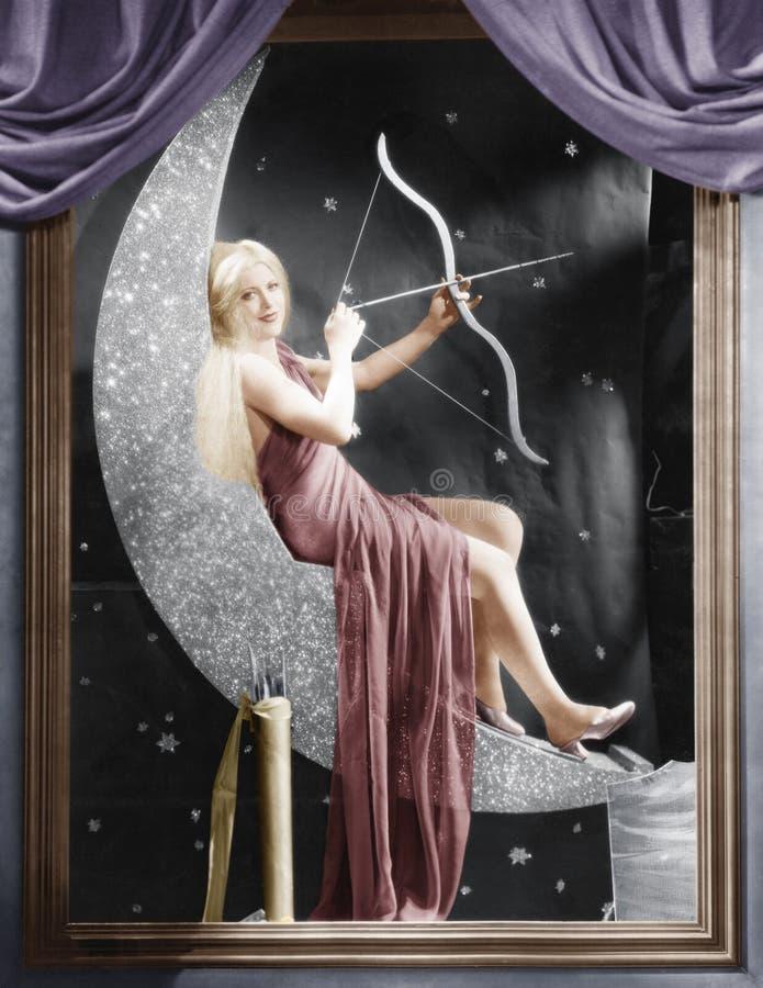 Vrouwenzitting op toenemende maan met boog en pijl stock afbeeldingen